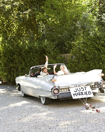 """A vintage car bears the classic """"Just Married"""" sign and tin cans."""