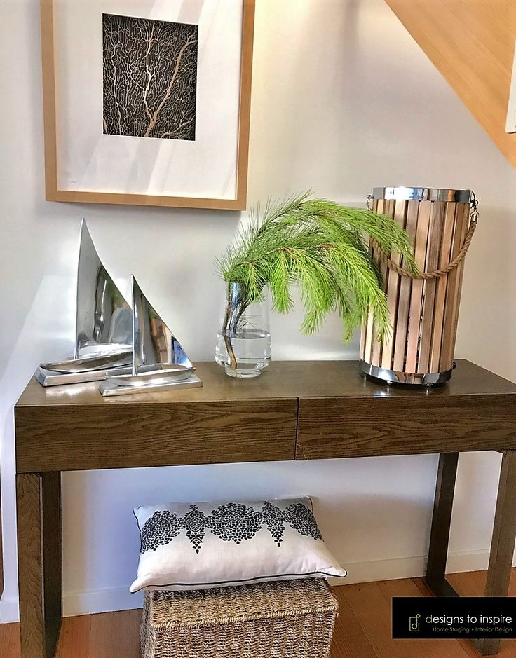 An under the stair nook is transformed into an attractive space with the right art and decor #designstoinspire #homestyling #consolestyle #nautical