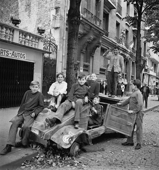 Liberation of Paris. Kids seen playing on a destroyed German kubelwagon August 1944.
