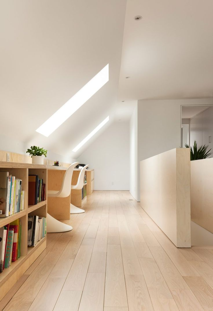 The upper storey of this house is defined by its roof pitch, which creates angled ceilings on the inside. At the top of the stairs, the architects created a small reading area and study space that is illuminated by two skylights.