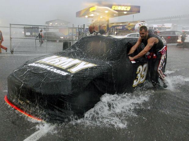 Mecânico tenta proteger e levar o carro de Ryan Newman para a garagem em meio à forte tempestade que atingiu o circuito oval de Pocono  Foto: AP