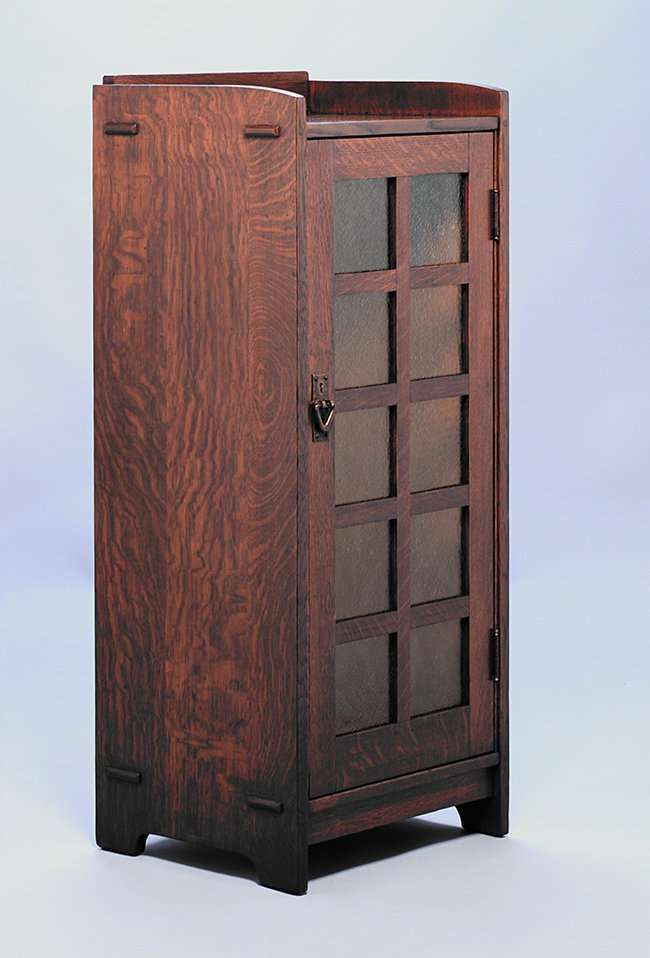 1528. Gustav Stickley one-door music cabinet with original amber glass. Refinished. Signed with branded mark. 47.5″h x 16″d x 20″w SOLD