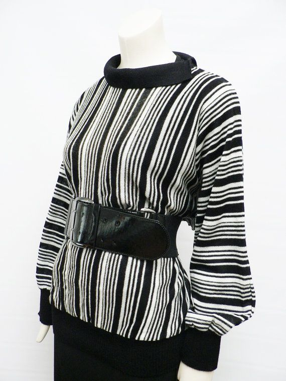 vintage 1980s knitted sweater top with black,white vertical stripes, large batwing sleeves and high rib waist. you can wear it more casual as a loose fit or dressed up with a nice belt ( belt on picture not included). made of a 100% polyacryl label: made in West-Germany in excellent