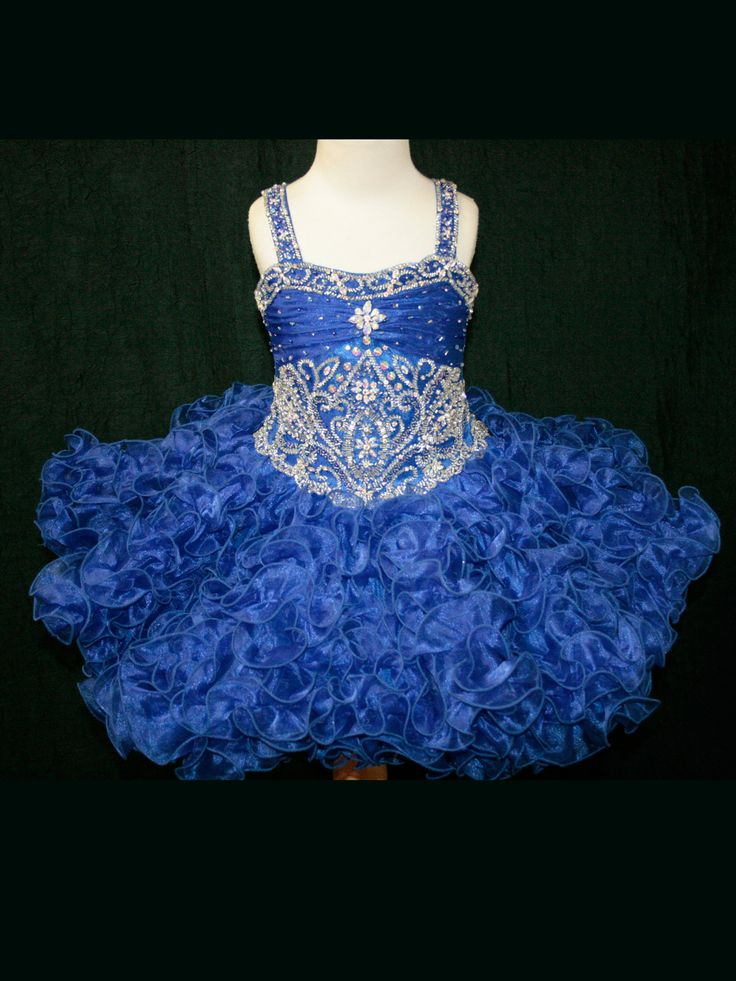 Available in black, red and royal, the Little Rosie pageant dress SR252 is an amazing short pageant dress for toddlers and girls with its beaded straps, a light capturing bodice that shows off an elegant rhinestone pattern, and a layered ruffled organza skirt perfect for taking home Grand Supreme!
