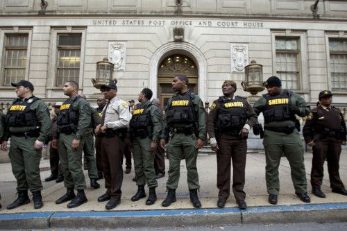 Sheriff officers stand guard in front of the courthouse main entrance as demonstrators protest outside of the courthouse after a mistrial of Officer William Porter, one of six Baltimore city police officers charged in connection to the death of Freddie Gray, on Wednesday, Dec. 16, 2015, in Baltimore. (AP Photo/Jose Luis Magana)