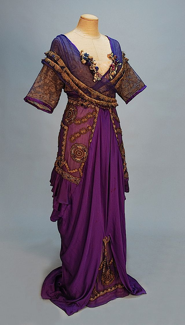 1911 - The lowest layer of this dress designed by Lady Lucy Duff Gordon, known as Lucile, appears to be a slip. The bodice has sheer criss-cross layers edged with ornamental rope. A layer of gold-decorated sheer material sits in between the under-garment and the criss-cross bodice. The dress appears to have a shallow vee waistline. The skirt may also have three layers - a gold-embroidered purple under-skirt beneath a draped and opened skirt beneath panels that match the under-skirt.
