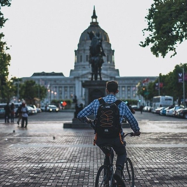 """""""Also at the Civic Center (see today's @Streetvogs post), a commuter on his bicycle heads toward's San Francisco's century-old City Hall. The original building was destroyed in the famous 1906 earthquake. Today, people can gather outside for a variety of events, including watching the Women's World Cup live. Go Team [insertyourfave]!!"""" @goodarrow3/@citywithdreams for @streetvogs"""