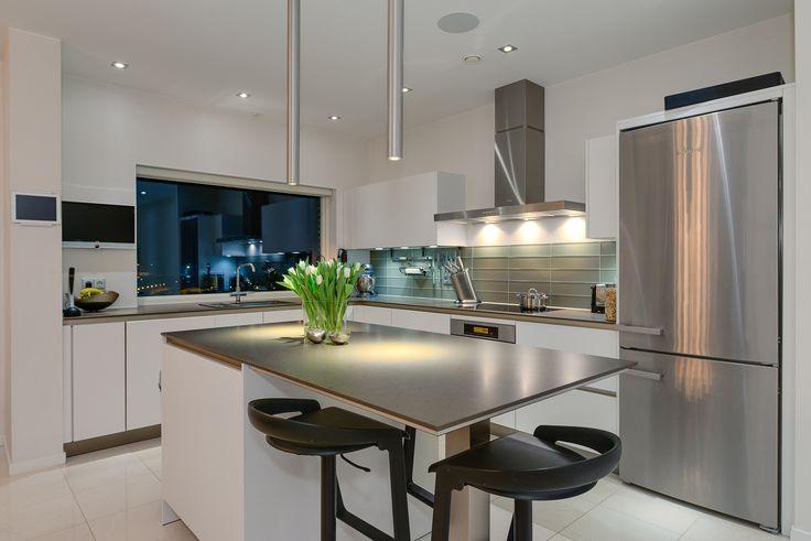 """Köket som går i vitt kommer från SieMatic, vars vision är att """"köket ska vara ett rum att trivas i"""". På Matadorgatan 2 får man ett kök som lever upp till den visionen och vars utrustning samt vy ut över havet bidrar till detta. Missa inte de dekorativa ljusarmaturerna ovanför köksön - så läckra!"""