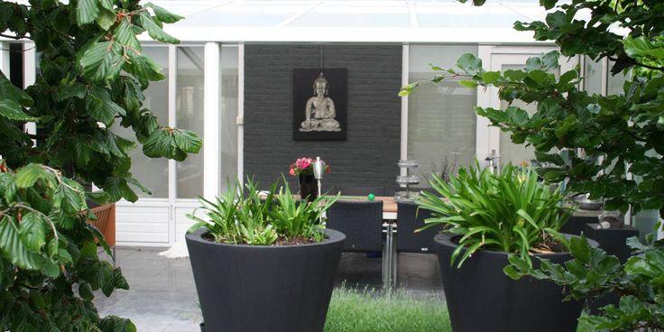 Kleine moderne achtertuin met prachtig zicht vanuit de openslaande deuren.
