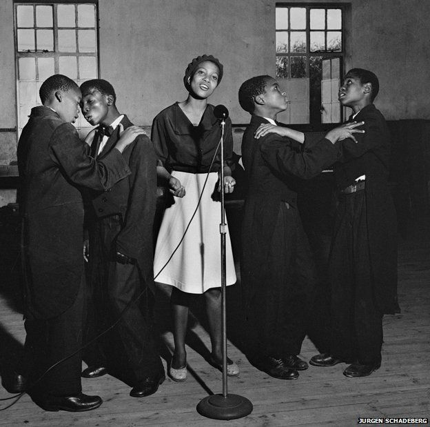 Singers in Sophiatown, 1954: People went to Sophiatown to listen to music. The scene there attracted people from across Johannesburg and musicians who later went on to become big stars, such as Miriam Makeba and Hugh Masekela, started their careers performing in Sophiatown's jazz clubs. But the South African government decided to clear the multi-racial neighbourhood to turn it into a whites-only area. When they realised how heavily armed the police were, ANC leaders - including Mandela…