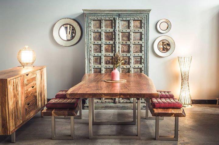 Acacia freeform table with antique door armoire.
