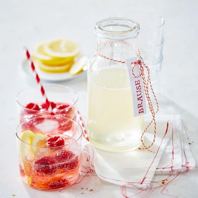 Sommerlimonade: Zitronensaft mit Holunderblütensirup mixen, mit Sprudelwasser, Himbeeren und Eiswürfeln aufgießen und erfrischen lassen.