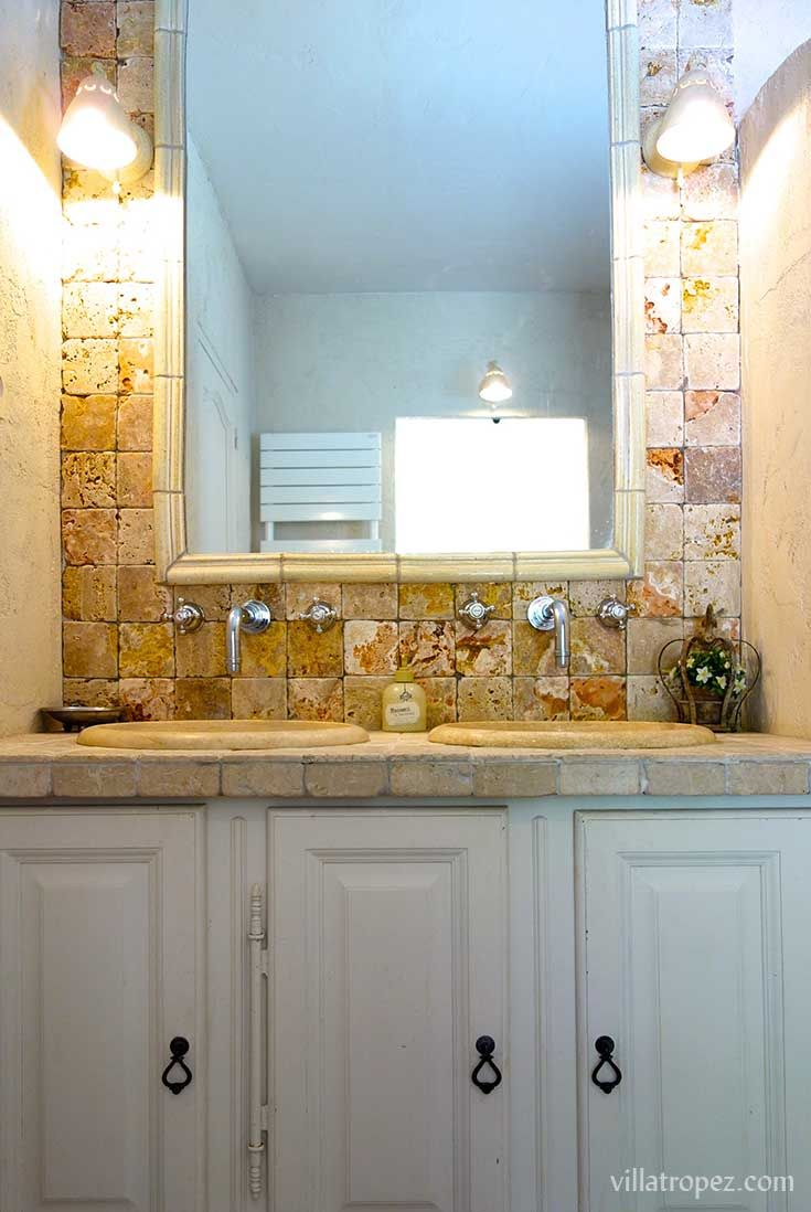 Tumbled travertine tiles, and french font embossed taps adorn the suite of this luxury provencal villa bathroom.   www.villatropez.com