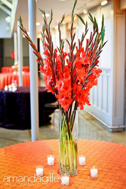 Centerpiece of Orange Gladiolus - Would be bigger and lusher, mixed in with some curly willow.