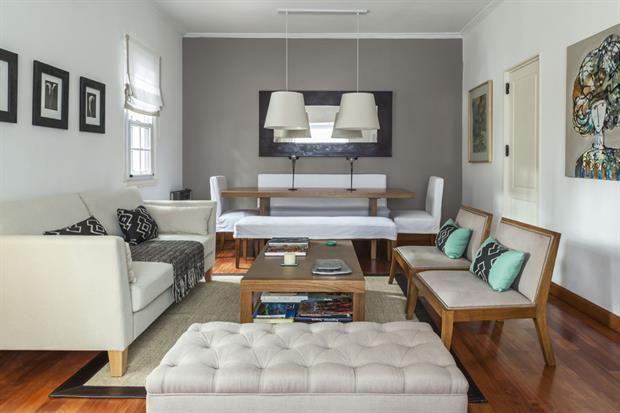 La pared gris enmarca a la mesa con los largos sillones de ecocuero blanco. Más acá, en el living, un sofá en color natural es acompañado por dos poltronas de madera tapizadas en un tono natural. / Archivo LIVING
