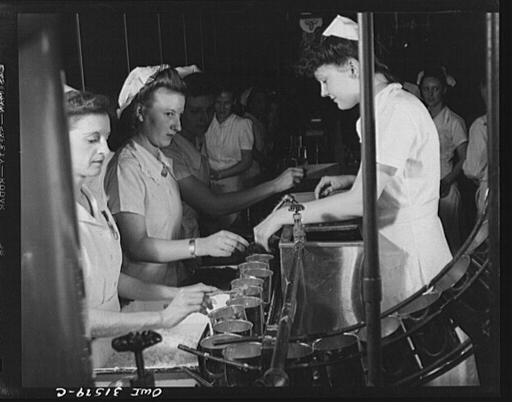 """Cincinnati, Ohio. Preparing canned pork (Russian: """"svinaia tushonka"""") for lend-lease shipment to the USSR at the Kroger grocery and baking company. Girls placing lard, spice and onions in cans before the pork is added. Right: Bonnie Williams, age twenty-one, who formerly worked in a shirt factory, has a husband in the U.S. Army June 1943"""