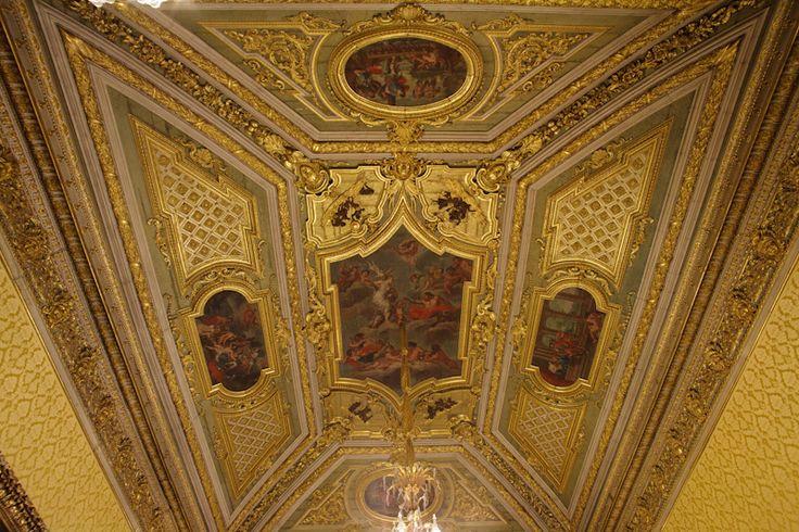 Detalhes do teto da Sala Dourada do Palácio Nacional de Belém, em Lisboa, Portugal. O suntuoso teto da Sala Dourada foi executado no século XVIII, é apainelado, tem uma pintura central alegórica e quatro medalhões nas quadras, rodeados de uma profusão de ornatos de talha dourada.   Fotografia: http://www.presidencia.pt/?action=12&id1=&id2=15&id3=51455