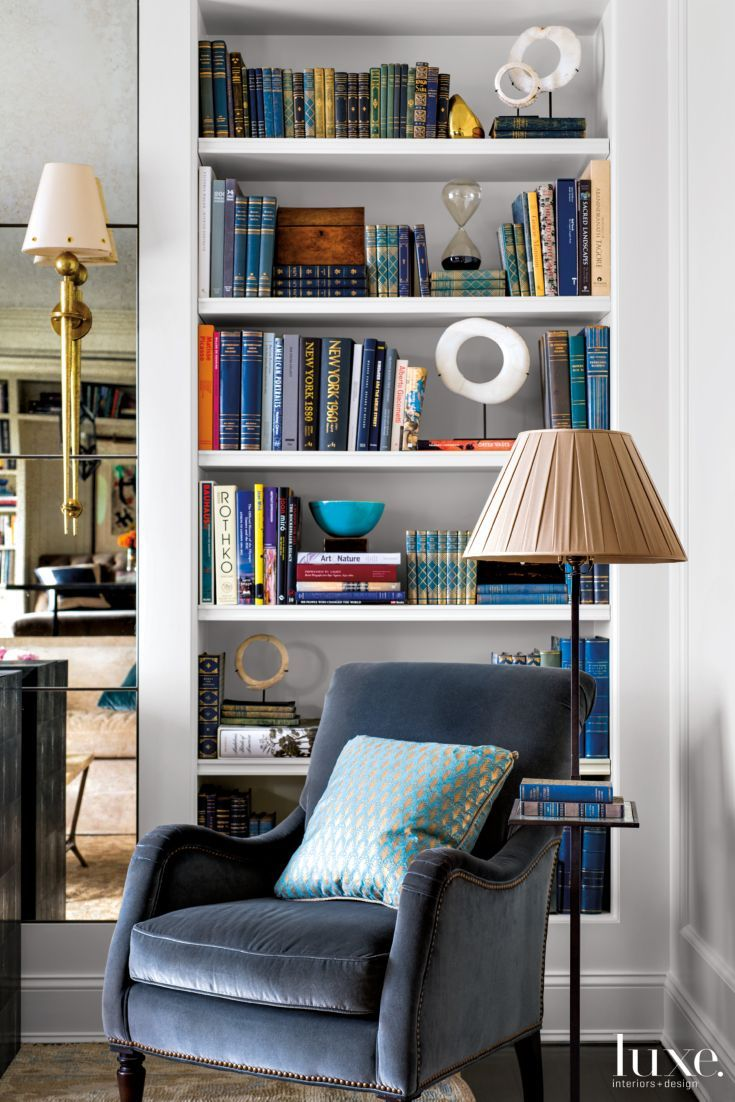 In the living room, interior designer Tammy Connor upholstered a Lee Industries chair in Schumacher velvet and topped it with a Fortuny pillow. The mounted bone disks in the bookcase are antique currency pieces from A. Tyner Antiques in Atlanta. Affixed to the antiqued-leaded-glass mirror, the bronze torcher sconce from Morateur Gallery in Los Angeles is a 1940s Art Deco fixture.