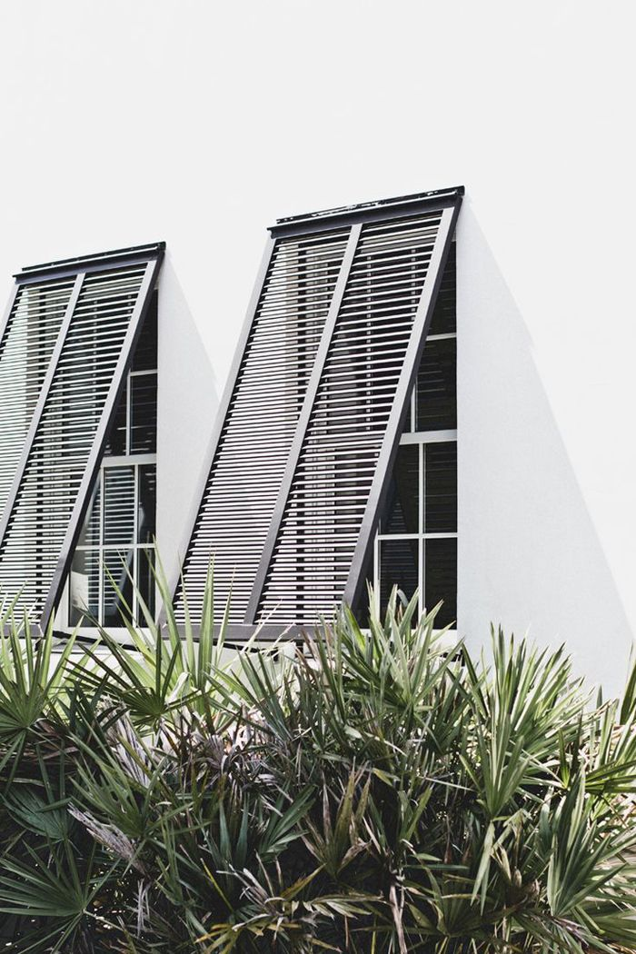 A crisp pair of Bermuda shutters in Tulum Mexico. When open this centuries old design helps protect interiors from the harsh sun as well as provide a clear view to the outdoors thanks to its specially angled slats. Photo via Veda House.