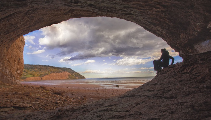 The Sandstone Caves of Blomidon Provincial Park Nova Scotia Canada.  The red sedimentary rocks exposed in the 600 ft-hgh cliffs date back   to the Triassic and are actually lake deposits. Since then the world's highest tides have carved numerous caves out of those cliffs