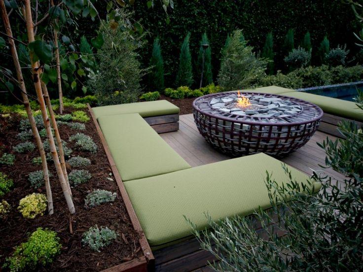 feuerstelle-garten-sitzplatzholzboden-sitzbank-holz-polster-gruen-pflanzen-baeume-zypresse