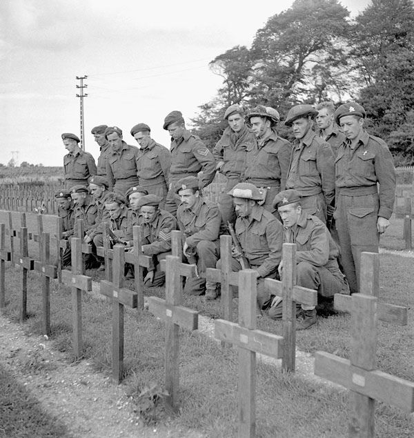 Major J. M. Figott and members of his company of the Royal Hamilton Light Infantry kneeling at the graves of Canadian soldiers killed at Dieppe on 19 August 1942. Dieppe, France, 1 September 1944.
