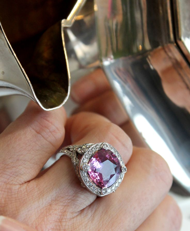Fabergé cushion-cut pink sapphire engagement ring set in white gold with diamonds. Surrounded by vintage antique silver milk jug and teapot with fun reflections. http://www.thejewelleryeditor.com/bridal/article/sapphire-engagement-rings-number-one-coloured-gem/ #wedding
