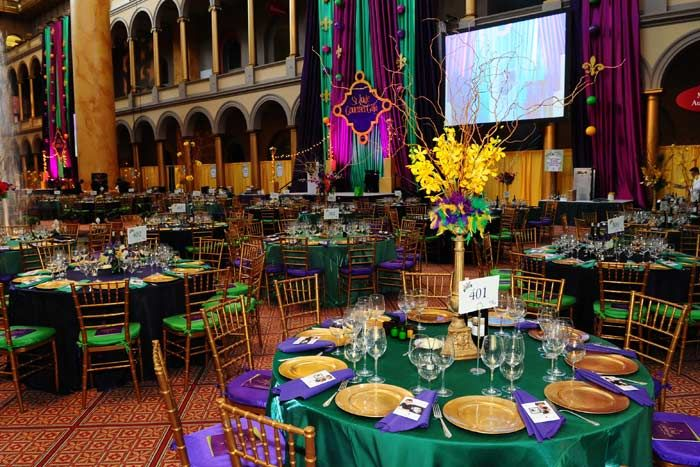 Tabletop floral arrangements incorporated feathers in Mardi Gras colors. | SocialTables.com | Event Planning Software