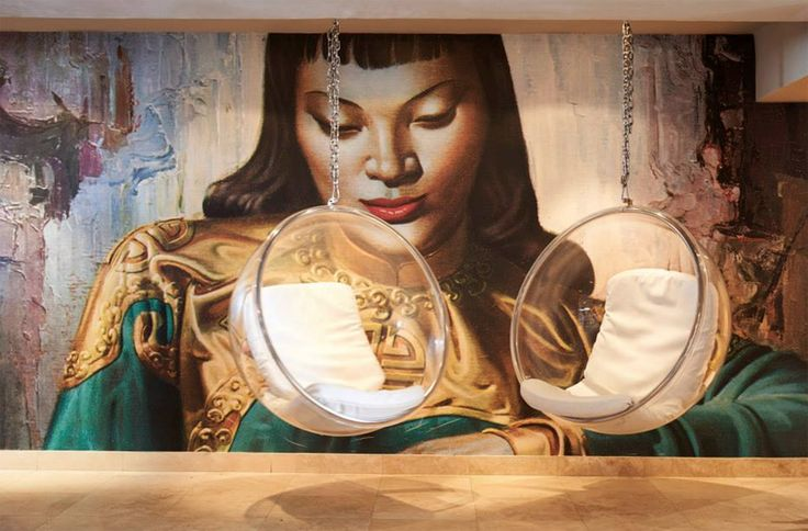 """LeRoi used the Tretchikoff """"Lady from Orient"""" as a statement piece in this room. The bold wallpaper compliments the furnishings exquisitely!"""
