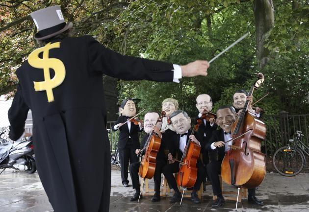 Un grupo de músicos activistas disfrazados con máscaras representan a los líderes miembros del Grupo de los 7 como una manera de protesta en...