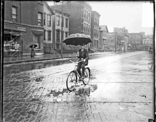 A man rides a bicycle in the rain during a street car strike in Chicago, c. 1915. Photograph from the Chicago Daily News.