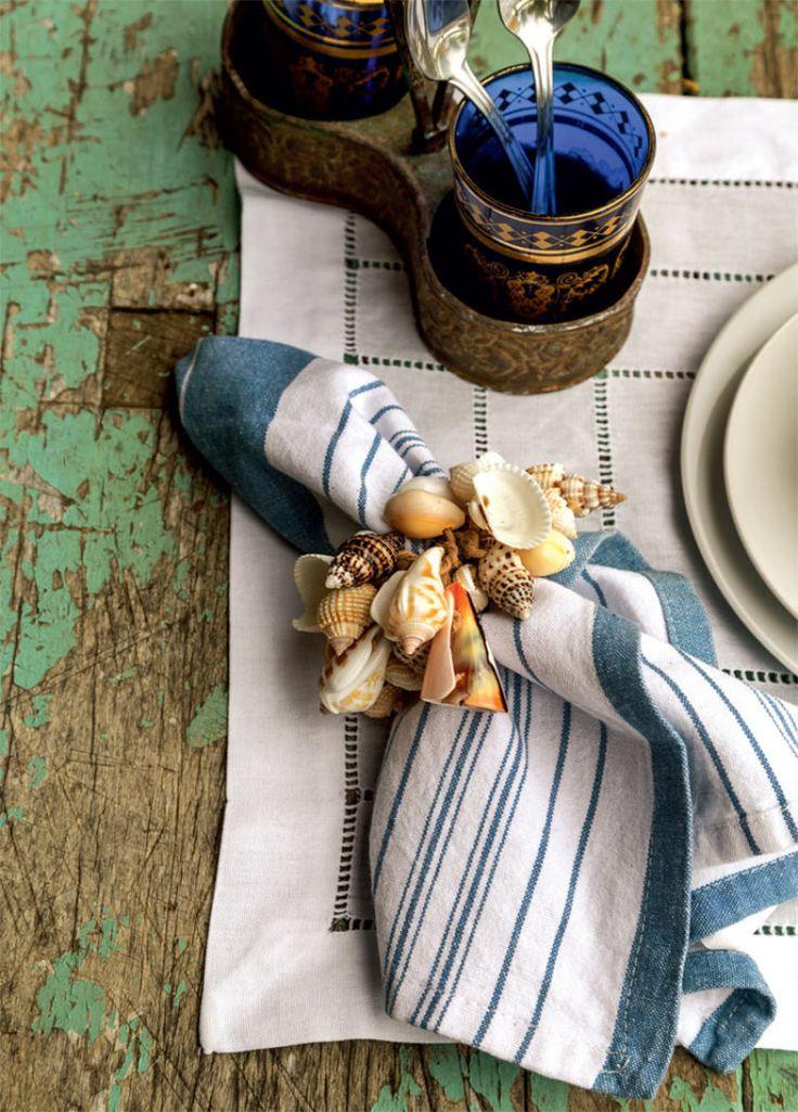 A mesa antiga guarda as marcas das facas usadas por pescadores ao limpar peixes. O anel de conchas (Cheia de Graça) envolve o guardanapo, comprado em Paris. Jogo americano de linho da Vanessa Bordados.