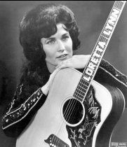 Loretta Lynn holds a guitar that has her name spelled down the fretboard circa 1961 in Nashville.