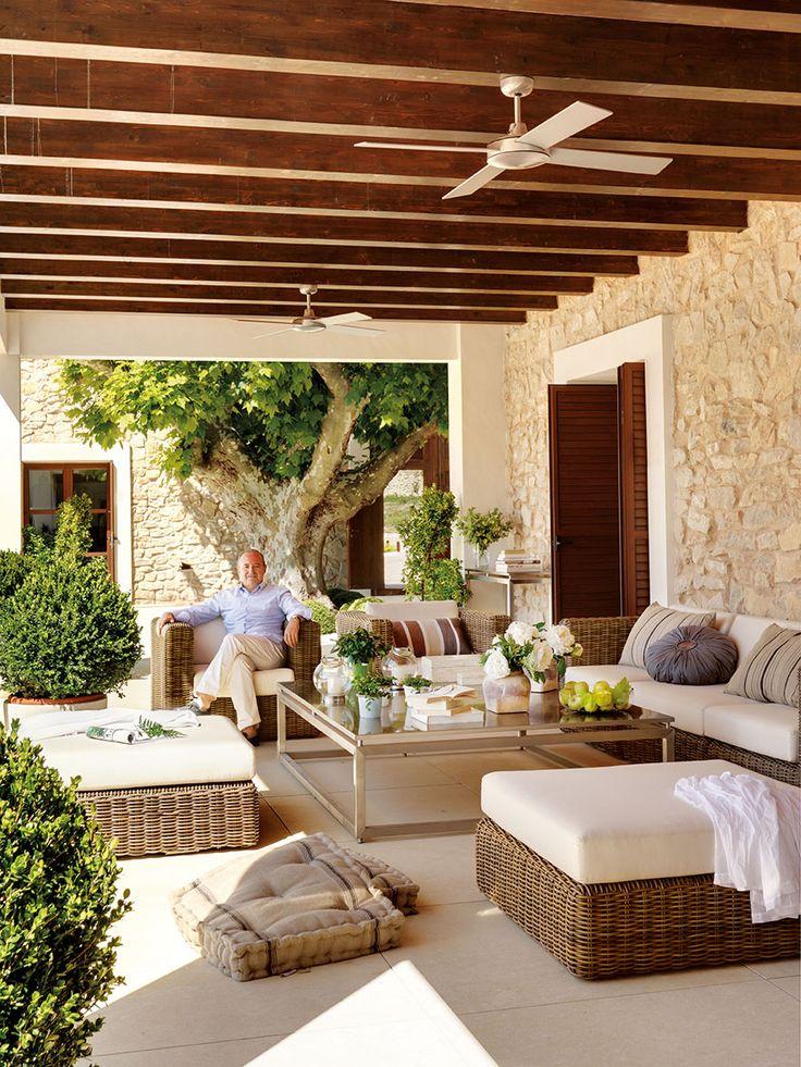 Porche con vigas de madera oscura con una zona de estar con sofás y butacas_00322389 3