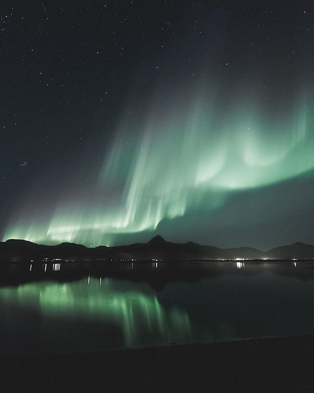 The northern lights reflects beautifully in the calm Reisafjord.