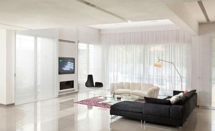 Sheer curtains soften this modern white minimalist living room