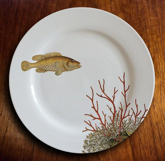 This 10.25 inch dinner plate features a beautiful golden fish with red spots. He is looking most curiously at a lovely red coral that grows before him. A lovely and graceful plate with a unique over-the-rim design that peeks out from behind your dinner. Hes also quite happy to hang on your wall. See our shop for wall hanging kits.  All of our pieces are decorated and kiln-fired at 1400 in our studio for a permanent, heirloom quality finish. They are food safe, dishwasher safe and microwave…