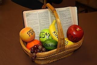 Beeldende bijbeltekst voor de vruchten van de geest: echt fruit met de vruchten erop geschreven en de bijbel geopend bij Galaten 5. // Fruit of the Spirit basket visual