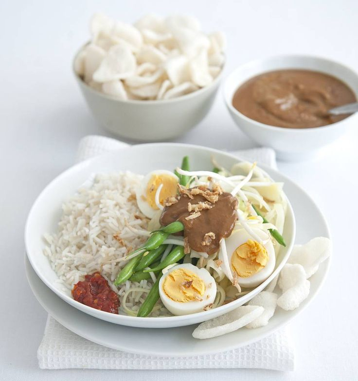 Kook de rijst volgens de aanwijzingen. Kook de eieren in 8 minuten hard. Kook de sperziebonen in 6 minuten beetgaar. Voeg na 4 minuten de kool toe.  Verwarm de pindakaas met de kokosmelk, de ketjap en peper (of sambal) en roer glad. Doe de taugé in een vergiet. Giet de bonen en kool erbij en laat uitlekken. Pel de eieren en halveer ze. Verdeel de rijst met de groenten en eieren over 4 borden.  Schep er een lepel pindasaus over. Serveer met de rest van de pindasaus. Lekker met gefruite…