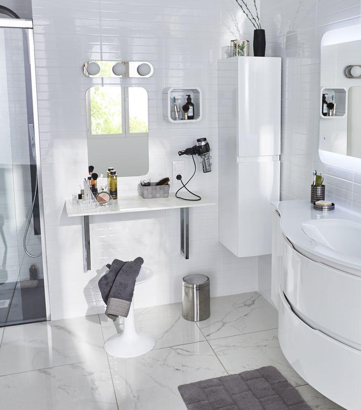 Aménager un coin coiffeuse pour tout avoir sous la main. Ajouter un porte sèche cheveux, un placard et un meuble avec vasque pour des rangements malins dans votre salle de bains.