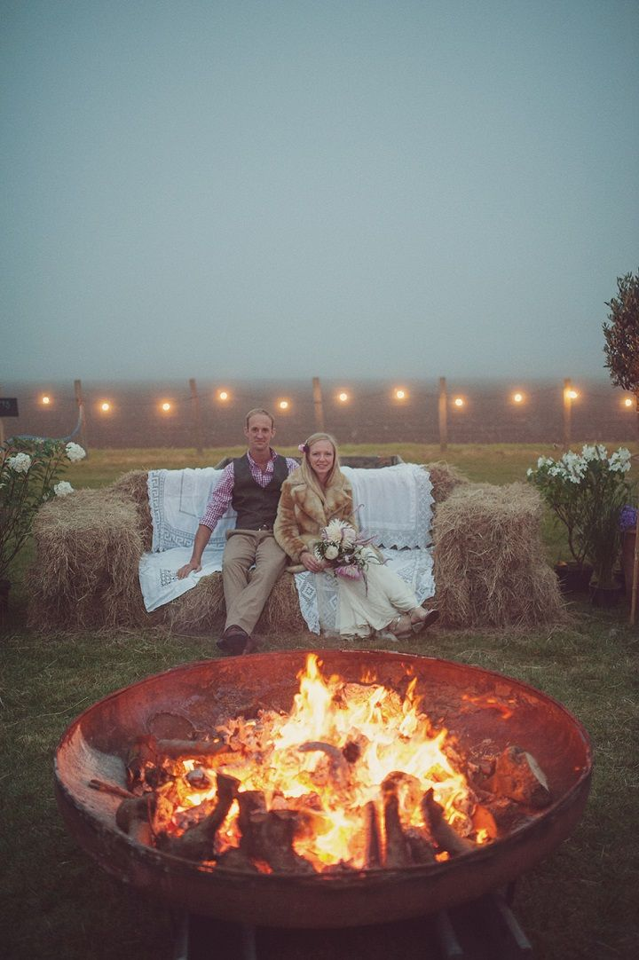 Unique wedding reception ideas on a budget  Outdoor hay bale seating area with fire pit lit up