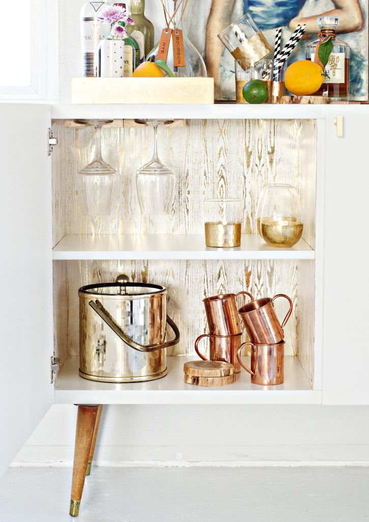 Here, two of IKEA's BESTA cabinets (they're no longer in stock, but any kitchen cabinet will work) in white high gloss combine together along with wooden peg legs to create the ultimate bar cabinet even Don Draper would be proud to own. Get the tutorial at Brittany Makes » - HouseBeautiful.com
