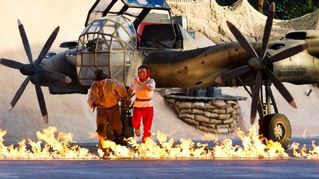 An exciting stunt show re-enactment of a scene from 'Raiders of the Lost Ark' with 2 actors running from a burning aircraft