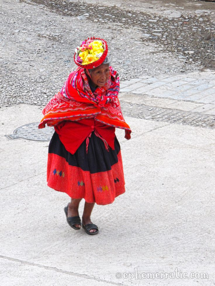Great outfit and flower-filled hat on this Quechua woman. From Ollantaytambo, Peru.