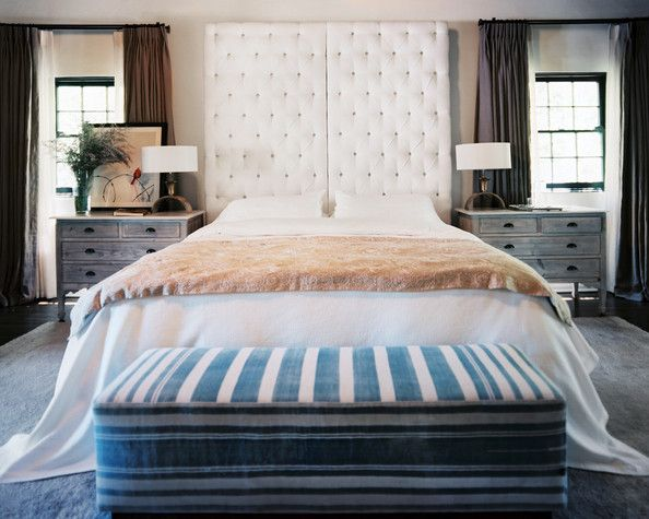 A serene master bedroom with a white tufted headboard.
