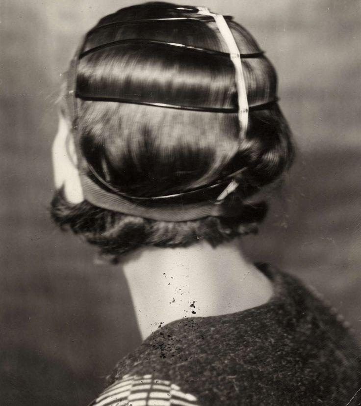 Kapsels, haarmode dames, haarverzorging, watergolven. Watergolfkap over het hoofd van een vrouw om golvend haar te maken. Plaats onbekend, 1934.