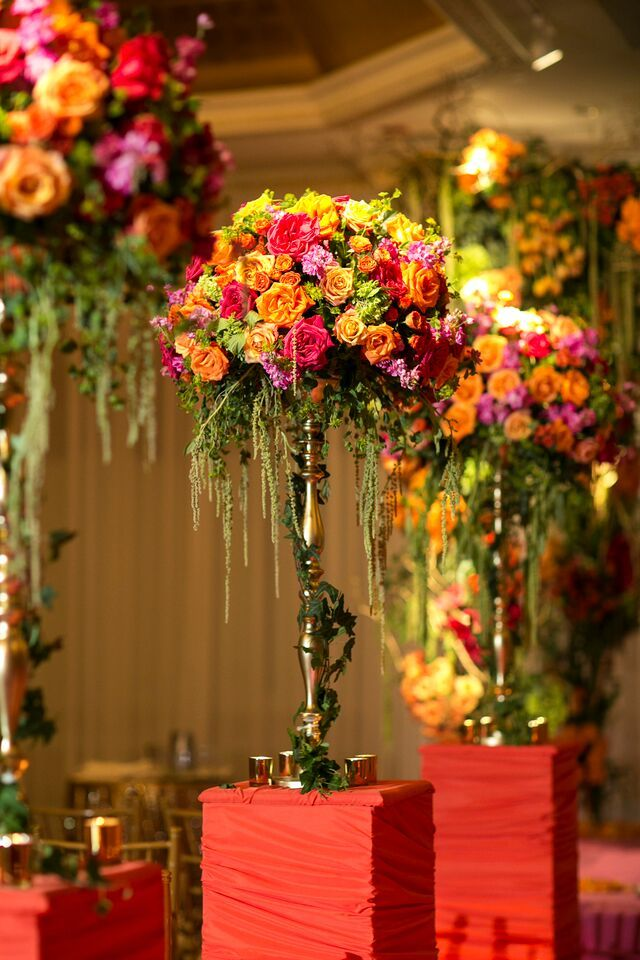 Multicolored flower centerpiece | Colorful fusion wedding filled with thousands of yellow, orange, and purple flowers: http://www.xaazablog.com/candy-colored-fusion-wedding-ritu-and-greg/ | Photography: Priyanca Rao Photography | Decor: Design House Decor | #weddingdecor #indianwedding #indianweddingdecor