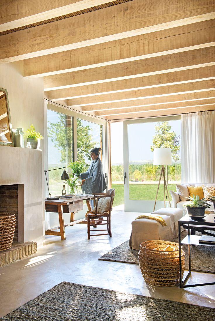 DSC2603 Persona. Salón con dos alfombras grises junto a la chimenea y zona de estudio junto a los ventanales que dan al jardín_DSC2603 Persona