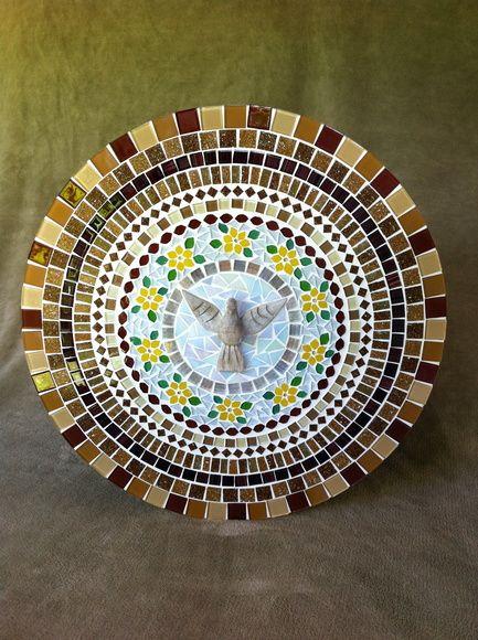 Mandala do Divino Espírito Santo em mosaico feito com pastilhas de vidro e pastilhas de vidro cristal. No centro, a imagem do Divino Espírito Santo em madeira patinada. É feita sobre uma base de mdf e vem com gancho para ser afixada em paredes. R$ 395,00