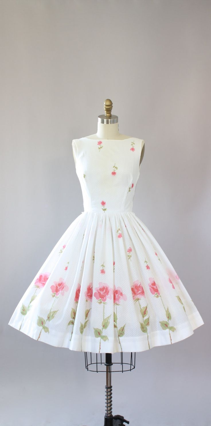Vintage 50s AMAZING Saks Fifth Avenue white swiss dot cotton dress with pink roses and green stems. Low back. Semi-sheer. Not lined, needs slip when worn. Metal zipper up back. Full skirt. Crinoline worn underneath skirt in photos for added fullness. Good vintage condition- a tiny rip on bodice near right sleeve opening has been professionally mended and patched by my tailor. It is not completely secure and barely noticeable! This piece has been cleaned and is ready to wear!  Label Saks…